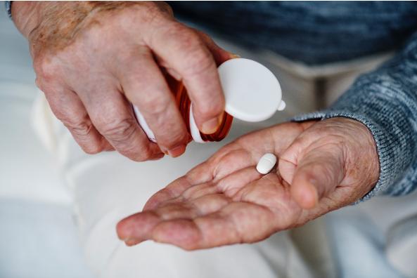 elderly person drinking a pill